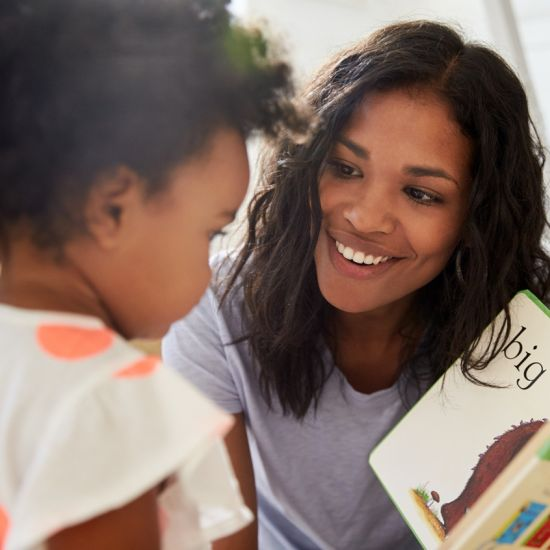 Woman with dark hair and skin reading book to a toddler